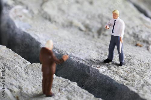 岩の亀裂と交渉するビジネスマンたち Canvas-taulu