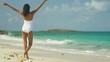 Beautiful ethnic Hispanic girl in white swimsuit on a tropical beach