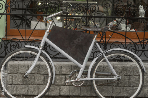 White bicycle at the fence on a pedestrian street.