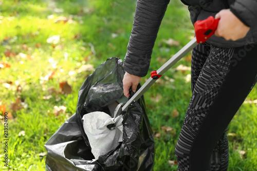 Fotografie, Obraz  Woman gathering trash in park