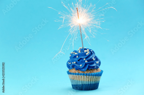 Photo  Tasty birthday cupcake with sparkler on color background