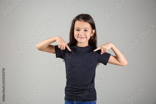 Cuadros en Lienzo Cute girl pointing at her t-shirt on light background