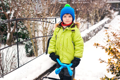 Fototapeta Little boy makes snowballs with snowball maker. Happy child playing with snow. Cold winter weather. Winter activities for kids. obraz na płótnie