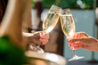 canvas print picture - two girls clink glasses of champagne on a beautiful summer terrace. sparkling champagne glasses. close up