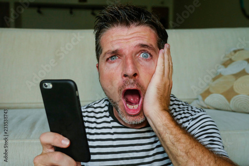 young perplexed and shocked man using mobile phone looking internet social media Wallpaper Mural