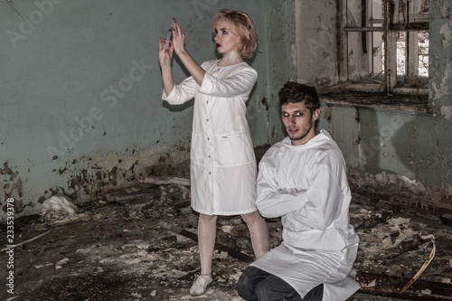Photo Asylum nurse or doctor with a syringe in hand is preparing to give an injection to an insane psycho patient in a straitjacket, inside of abandoned ruined hospital