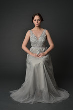 Full Length Portrait Of Brunette  Girl Wearing Long Silver Ball Gown. Seated Pose On Grey Studio Background.