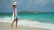 Beautiful ethnic Hispanic girl wearing white sun dress on ocean beach