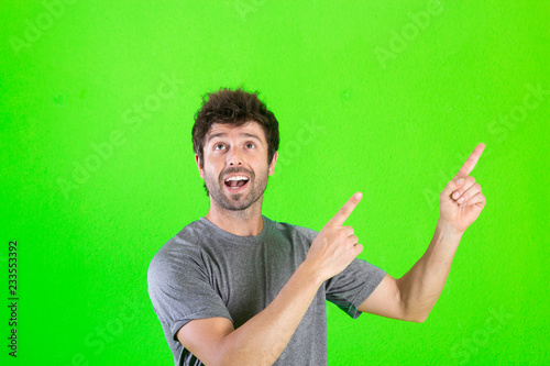 Fotografía  Young handsome man over green background amazed and surprised looking up and pointing with fingers