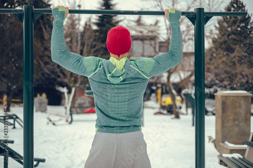 Valokuva  Man doing chin ups outside on a snowy day