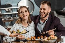 Smiling Couple Eating Sushi Ro...