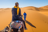 Berber nomad and a young girl riding camel in Sahara desert, Morocco