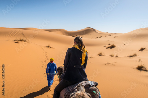 Berber nomad and a young girl riding camel in Sahara desert, Morocco Canvas-taulu
