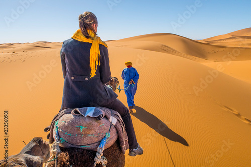 Berber nomad and a young girl riding camel in Sahara desert, Morocco Canvas Print