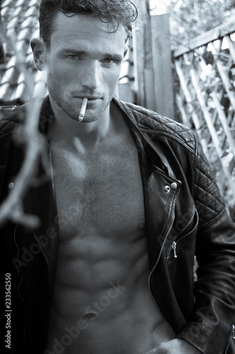 Handsome blonde man with open leather jacket revealing sixpack abs smoking cigar Wallpaper Mural