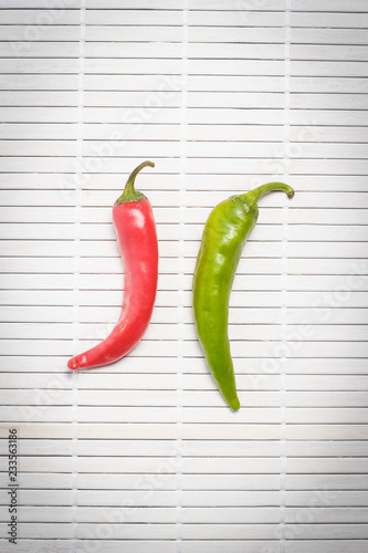 One red and green hot chili pepper on white table