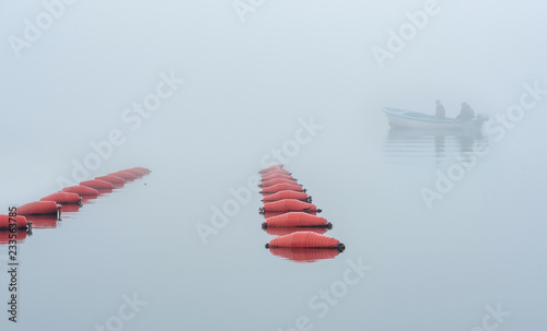 Small fishing  boat in the Village at Boka Kotor Bay in the morning fog, Montenegro