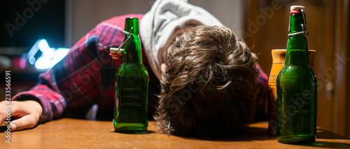 Fotografering young drunk man with glass and bottle of alcohol lying on the table  f