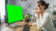 Beautiful Young Girl Works On A Green Mock-up Screen Personal Computer While Sitting At Her Desk In The Cozy Apartment.