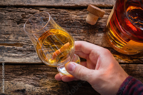Fotografía hand holds whiskey in a glass for tasting on a wooden background