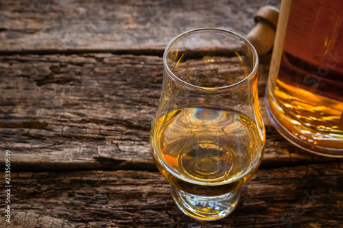 glencairn whiskey glass with single malt whiskey with space for text on a wooden background