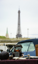 Flea Market In Paris (France). Vintage Car Model And Other Stuff On A Stall With A View Of Seine River Banks And Eiffel Tower.