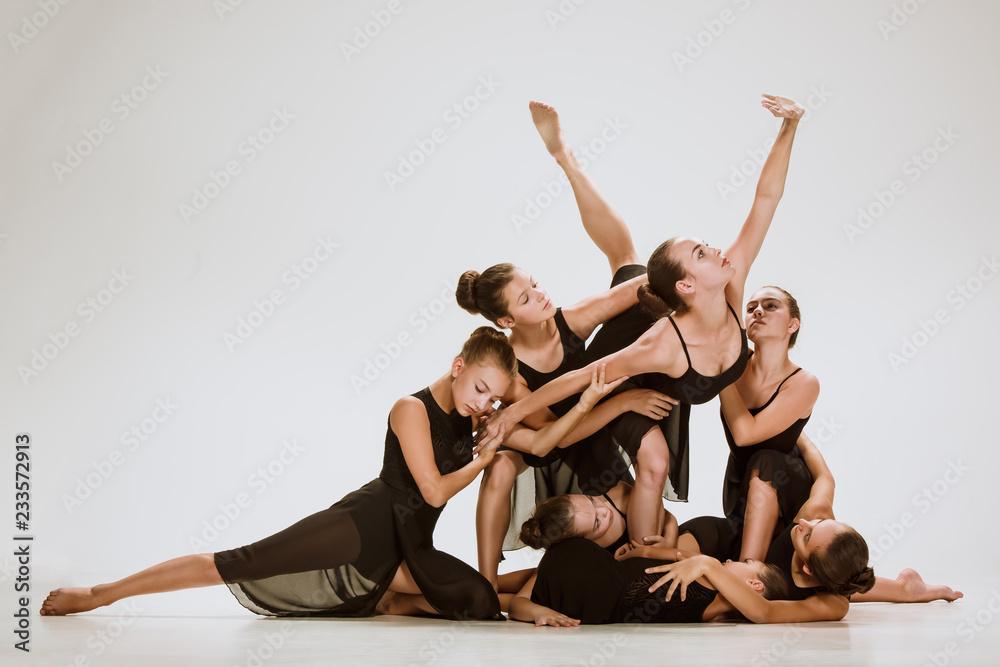 Fototapeta The group of modern ballet dancers dancing on gray studio background