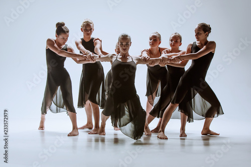 the-group-of-modern-ballet-dancers-dancing-on-gray-studio-background