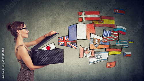 Fotografía  Woman speaks different languages opening a box with international flags flying a