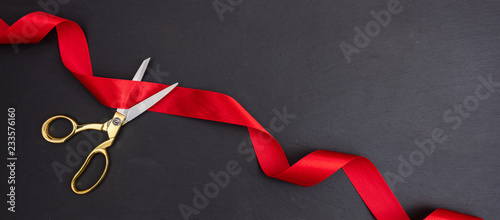 Stampa su Tela Scissors cutting red silk ribbon against black background, banner
