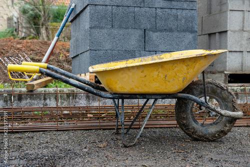 Obraz na płótnie yellow wheelbarrow  in construction site after use.