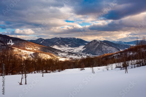 beautiful winter landscape of Carpathians. Village down in the valley in dappled light. gorgeous evening cloudy sky above the ridge.
