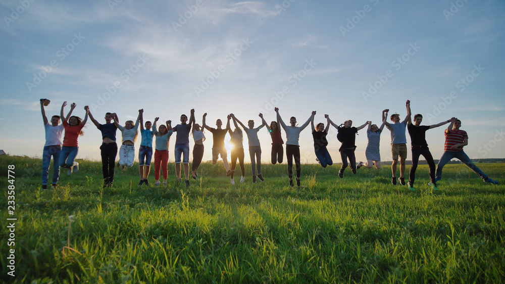 Fototapety, obrazy: Group of best friends and students jumping outdoors. Sunset with sunshine rays.