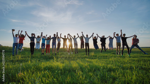 Group of best friends and students jumping outdoors. Sunset with sunshine rays.