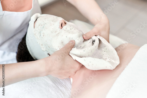 The process of removing the jellied alginate mask from the