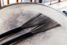 Close-up Of Pair Of Black Drum Brushes On A White Shabby Drum. Concept Concert, Live Music, Performance, Musical Evening In A Restaurant