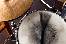 Close-up Of Of Black Drum Brush On A White Shabby Drum And а Part Of Golden Cymbal. Concept Concert, Live Music, Performance, Musical Evening In Restaurant