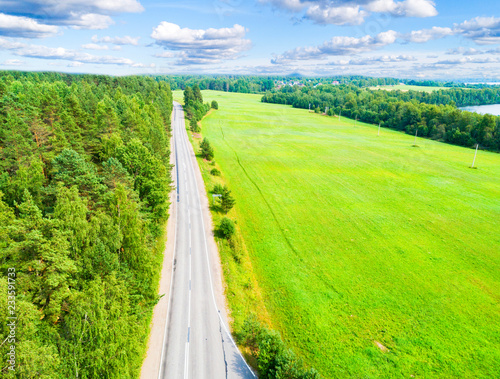 Aerial view of a country road in the forest with moving cars. Landscape. Captured from above with a drone. Aerial bird's eye road with car. Aerial top view forest. Texture of forest view from above.