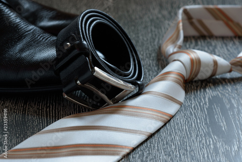Fotografía  Men's accessory set black boots, leather belt and tie on grey wooden background