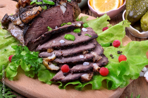 Baked ham of elk meat cut into slices topped with greenery and cranberries on the salad leaves