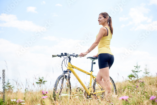 Young Happy Woman Cyclist Standing On A Grassy Hill With
