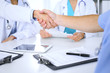 Two doctors shaking hands to each other at meeting. Teamwork and agreement in medicine