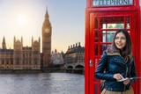 Fototapeta Londyn - Weibliche Touristin in London vor einer roten Telefonzelle schaut auf den Big Ben Turm und Westminster Palast beim Sightseeing