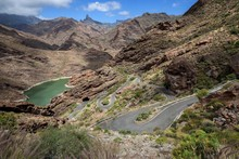 Volcanic Barren Mountain Landscape With A View Of The Reservoir Presa Del Parralillo, Winding Road GC606, At El Carrizal, Behind Cult Rock Roque Bentayga, Gran Canaria, Canary Islands, Spain, Europe