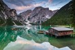 Stilt house in lake with boats and mountain landscape, Dolomites, Italy