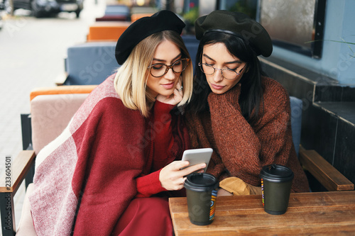 Valokuva  Portrait of two young women in an outdoor cafe, drinking coffee