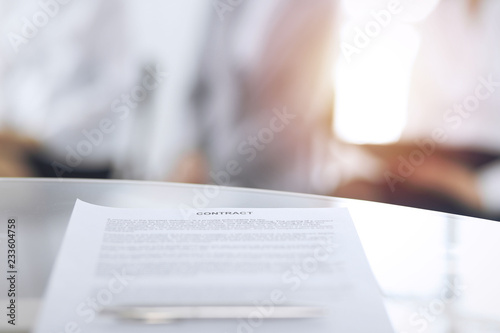 Fototapety, obrazy: Contract with a pen and blurred business people on the background, close-up. Female candidates waiting for interview at queue