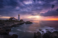 Sunshine Breaking Through Dark Clouds At Portland Head Lighthouse In Maine
