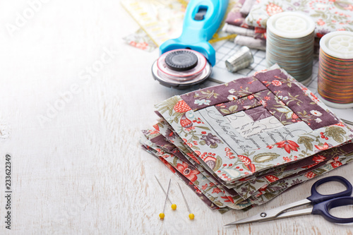 Fotomural  Patchwork log cabin blocks, stack of blocks, sewing accessories on white wooden