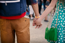 Midsection Of Couple Holding Hands While Walking At Amusement Park